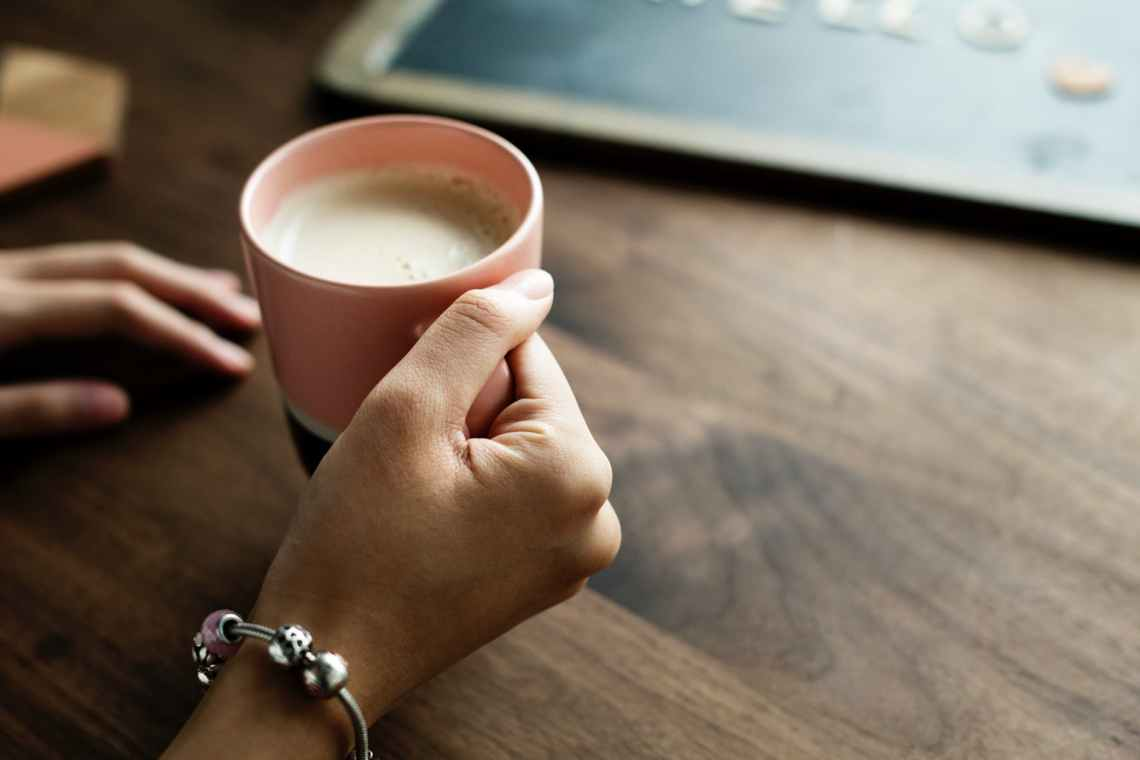 person holding pink ceramic mug