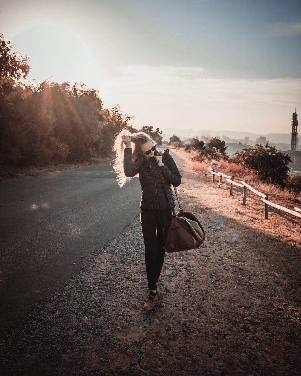 photo of woman walking while holding her hair